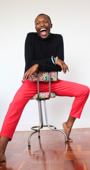 Ayabonga Ngoma (ALN) sitting on floral chair laughing wearing black polo neck and red pants