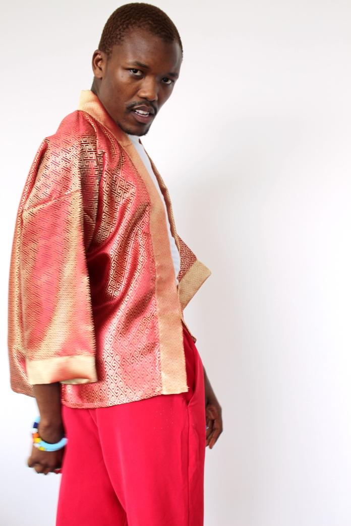 Ayabonga Ngoma standing sideways wearing red and gold kimono
