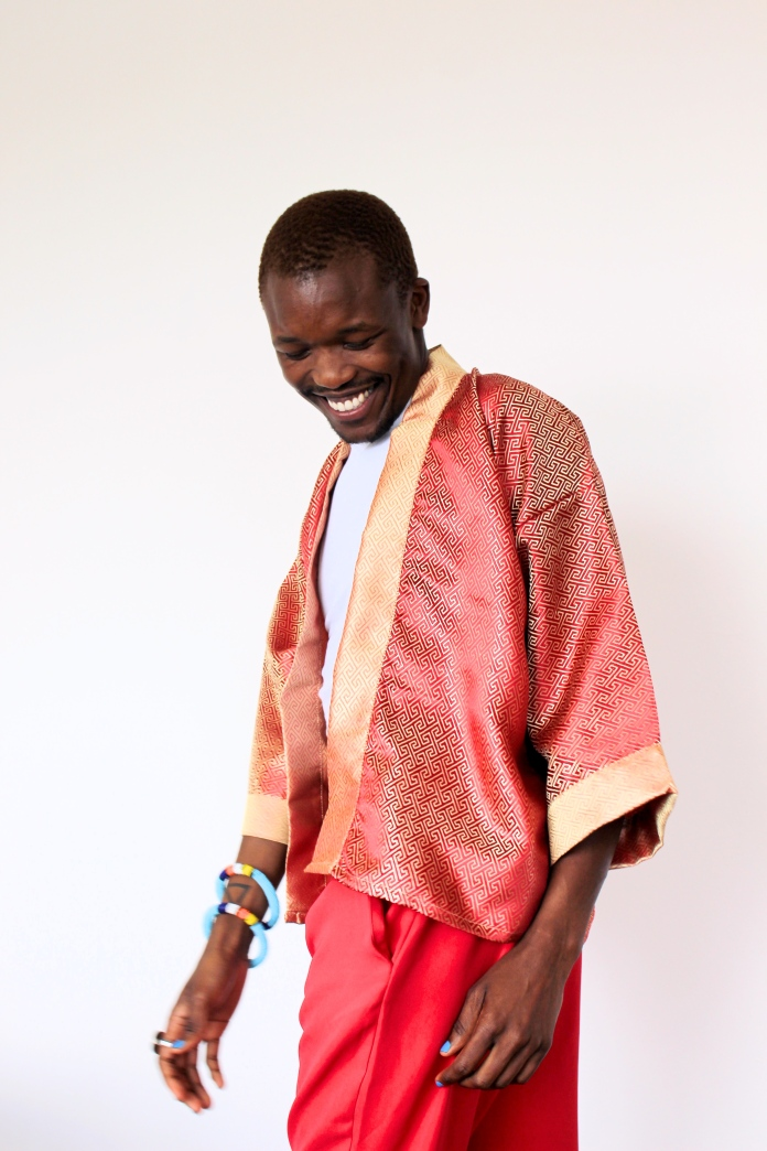 Ayabonga Ngoma (ALN) laughing with head looking down wearing red and gold kimono