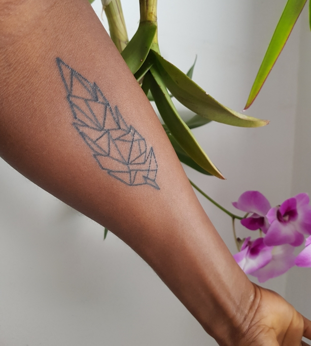 Arm with geometric feather tattoo