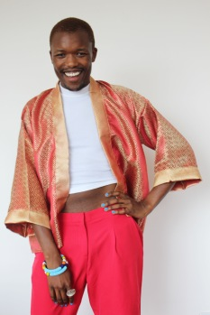 Ayabonga Ngoma (ALN.) standing smiling with arm on left hip in red and gold kimono
